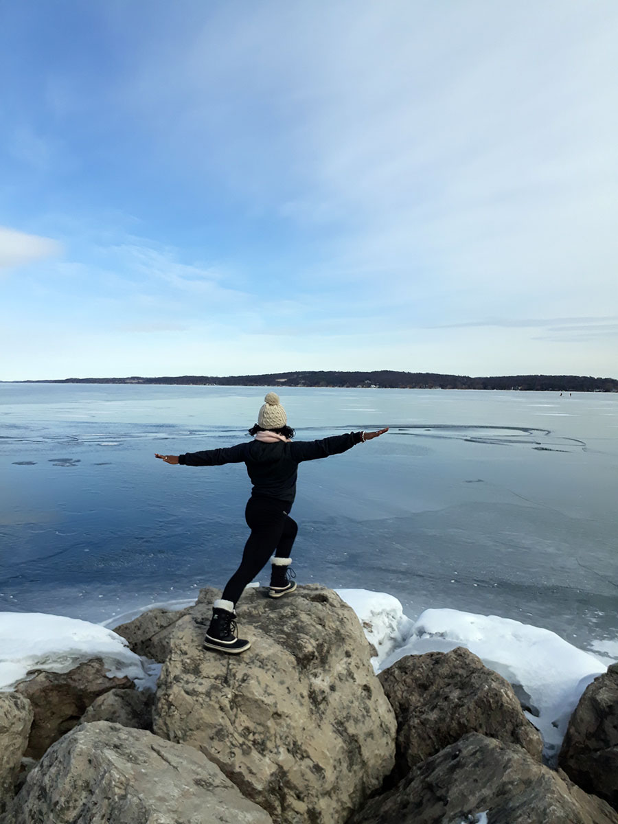 Janet Haughton Quarshie In A Yoga Pose On A Rock In Winter In Traverse City